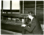 NBS Radioactivity Laboratory worker manipulating the balance used to weigh radium containers at a distance of 10 feet